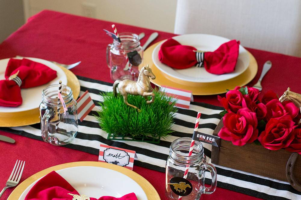 Kentucky Derby tablescape with grass patches and DIY gold spray painted toy horses.
