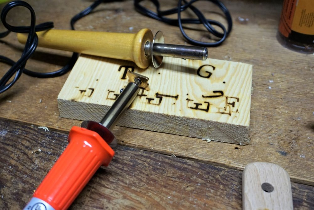 Heat up your wood burning tool with alphabet letter.