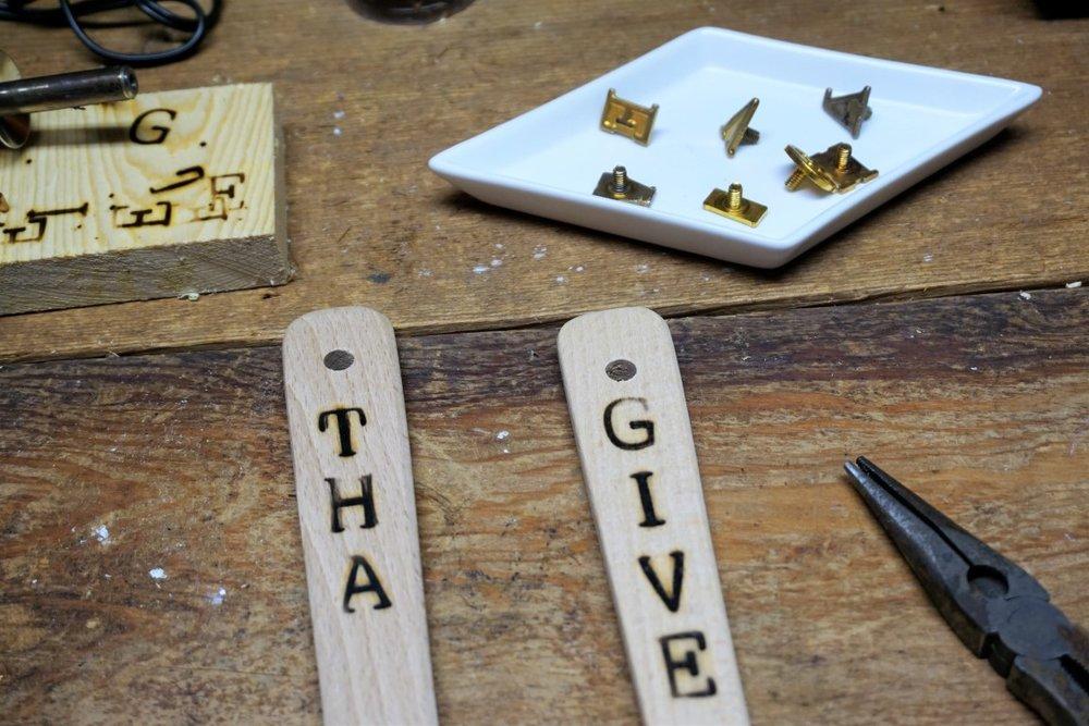 Wood burned letters on wooden utensils.