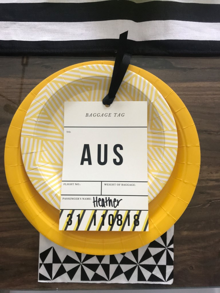 A luggage tag in yellow, black, and white makes a perfect travel themed placecard.