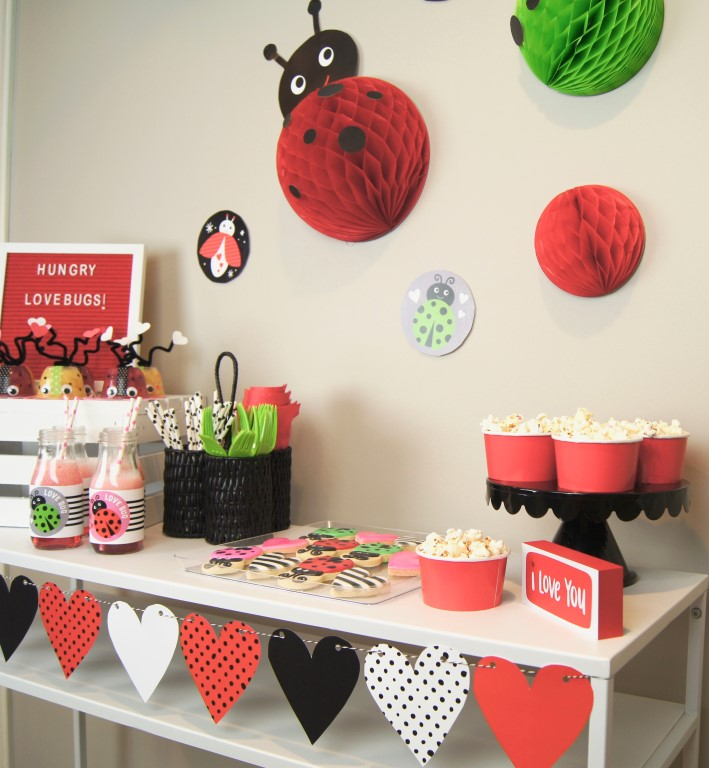 DIY love bug backdrop using free Valentine printables, red and green honeycombs.