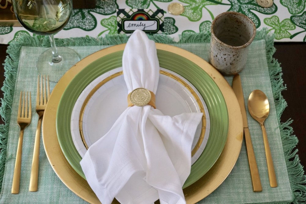 St. Patrick's Day place setting with green placemats, gold charger, green plates, and gold silverware.