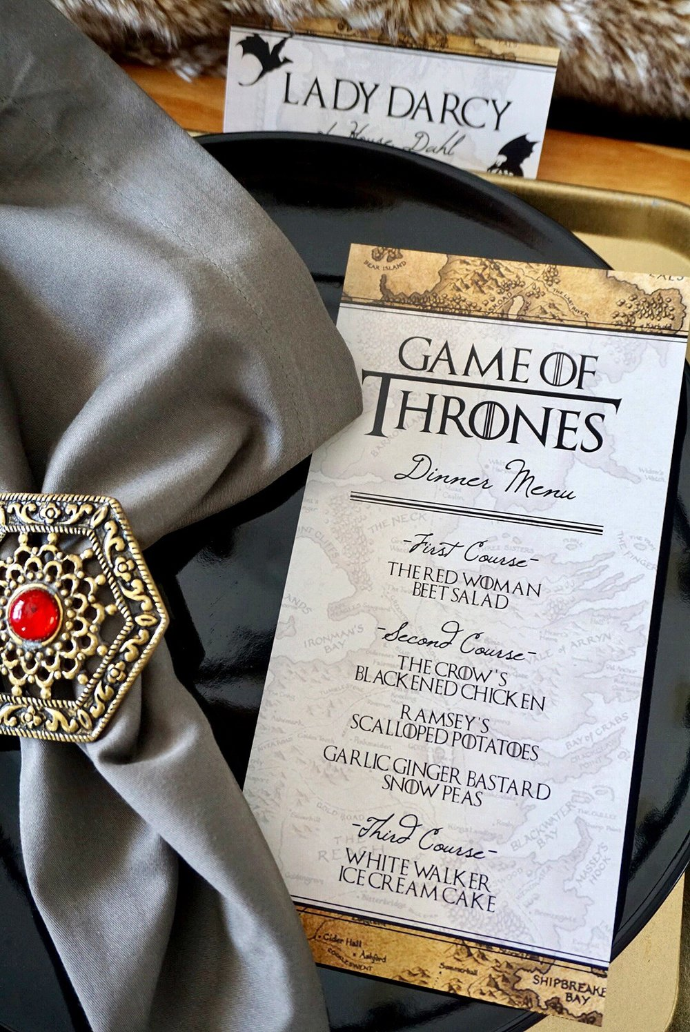 Gold napkin ring with red jewel, grey linen napkin, and Game of Thrones themed dinner menu.