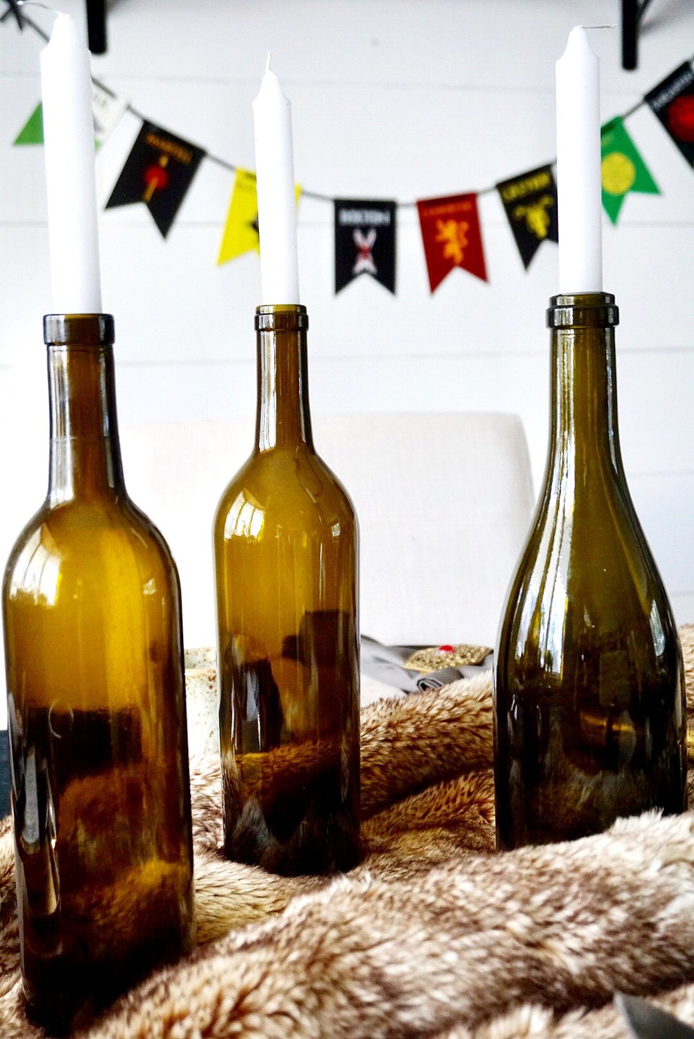 Empty wine bottles with candlesticks make a great centerpiece for a Game of Thrones watch party.
