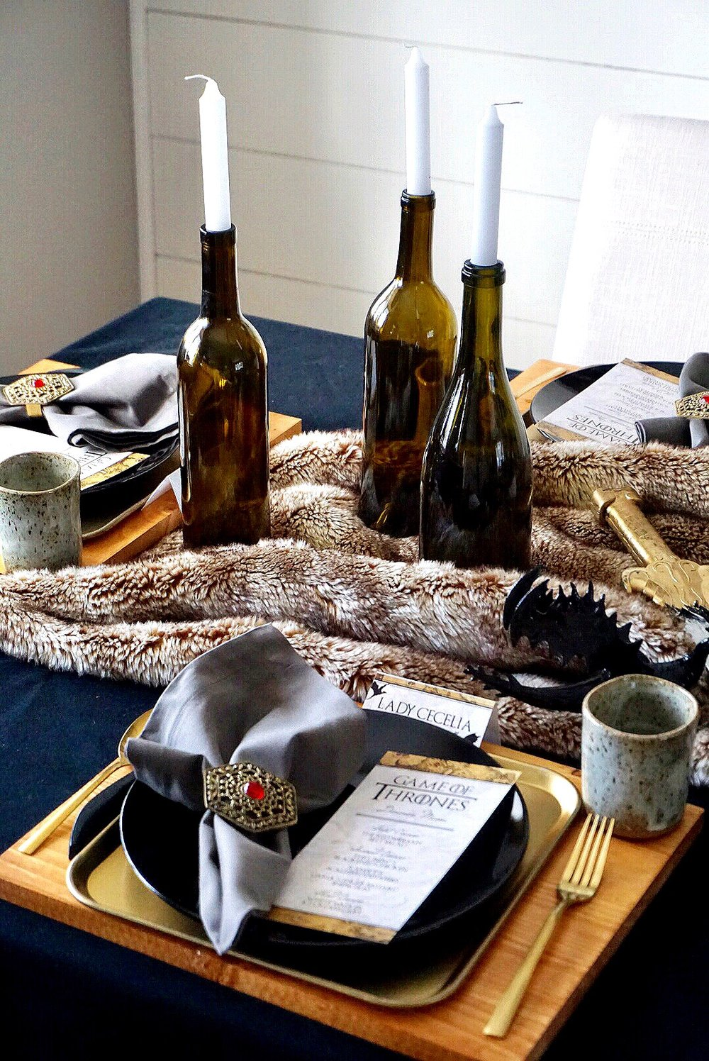 Wood chargers, gold tray, and black plates along with gold utensils make the perfect place setting for a Game of Thrones dinner party.