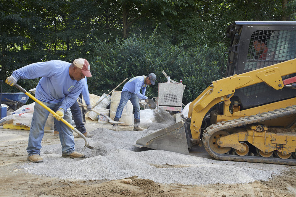 Workers shoveling gravel in their matching Falkner Gardens shirts.
