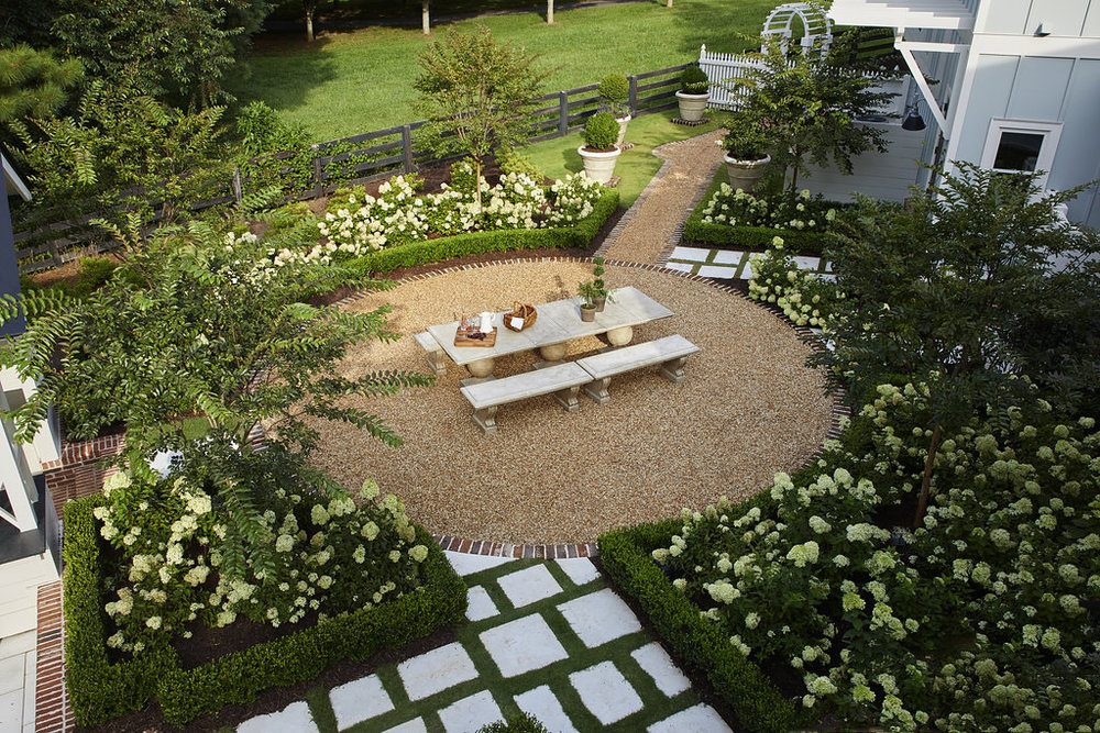Aerial view of outdoor entertainment area surrounded by custom stonework, hydrangea bushes, and shrubbery.