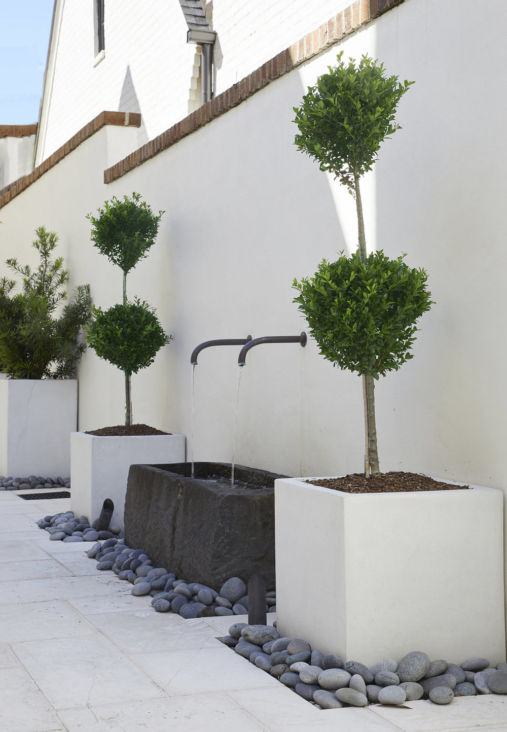 Custom built fountain into the wall - two large spigots going into a large custom built base.