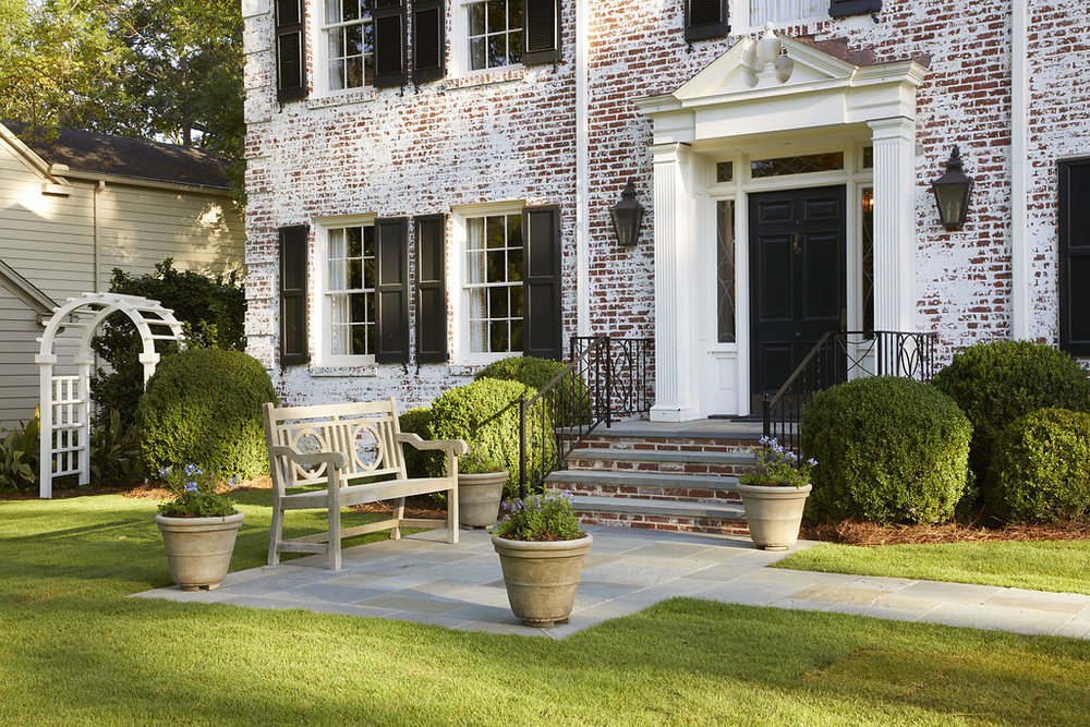 Custom pots made in Alabama line the walkway to the front door of this home.