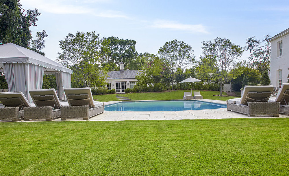 View of the pool from the green grass.