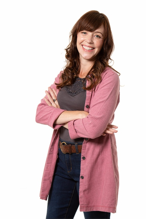 kate drake, lady standing and smiling in pink sweater with blue jeans and white background