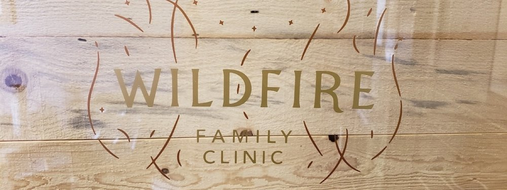 wildfire family clinic logo on glass in front fo wood wall