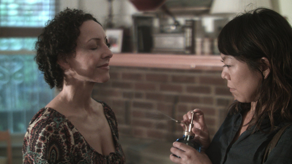 """In ANYA, the Narval people speak their own language. In scene, LIBBY (Ali Ahn), a Spanish-speaker, gets a cultural and linguistic lesson when her new mother-in-law (SARA, Ana María Jomolca) teaches her that """"narval"""" means seawater."""