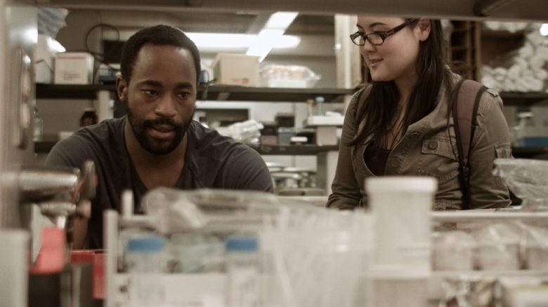 DR. SEYMOUR LIVINGSTON (Motell Foster) defends his ethics to his research assistant, RIKA ENDO (Olivia Oguma)