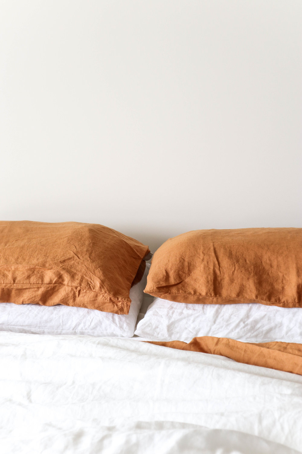 Products shown: Standard pillow cases in Optic White and Tobacco, Duvet Cover in Optic White, Flat Sheet in Tobacco.