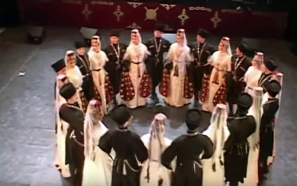 Simd / Ossetia - Simd is an Ossetian folk group dance. Its beauty lays in the strict graphic outline of the dance, the contrast between black and white costumes, the softness of movements, the strictness of line formations, and the harmony created by all of the above.