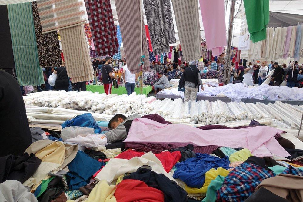 Istanbul | Karakoy | Karakoy market | Asian coast of Turkey | boy in market sleeping on fabric rolls |