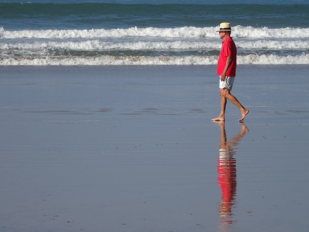 Atlantic ocean | Man with red shirt walking on the beach | France |©sandrine cohen