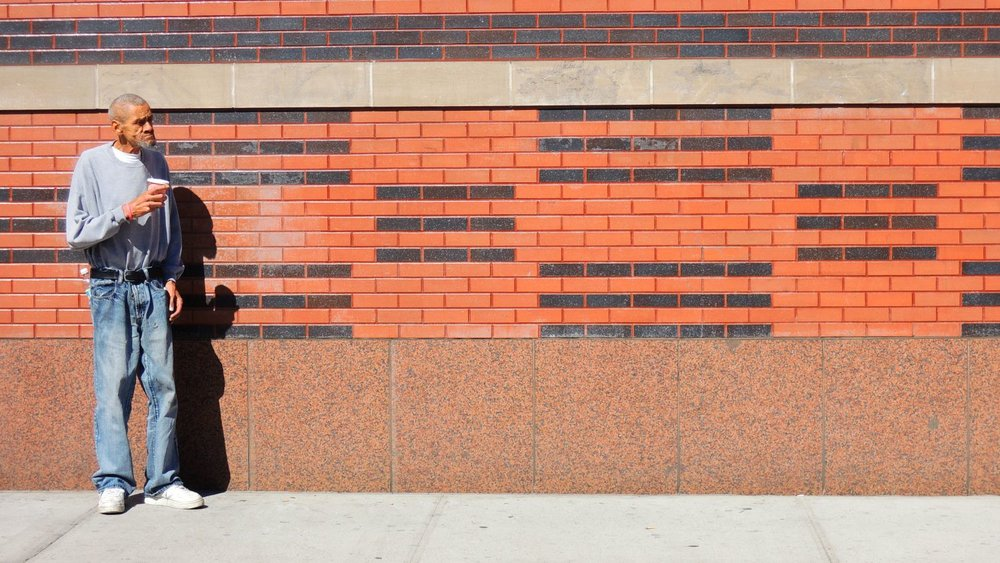 Harlem | New York | Poor man on a brick wall | photo sandrine cohen
