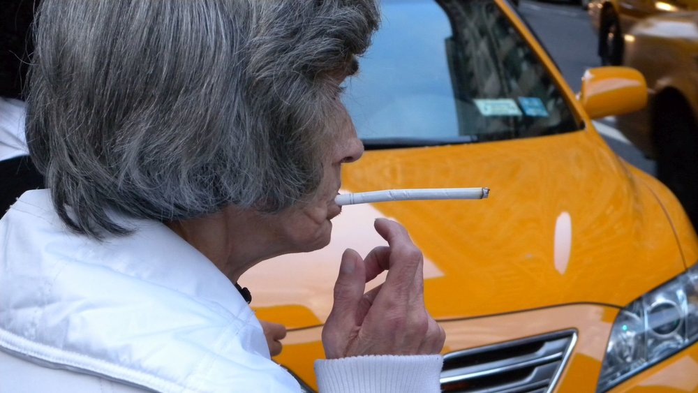 New York | Woman smoking long cigarette | Yellow taxi | photo sandrine cohen