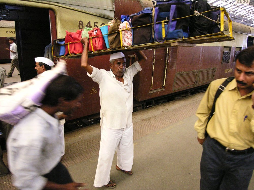 Mumbai - Bombay | Mumbai dabbawala | Dabbawala at railways station | Churchgate station | Man carrying lunch boxes | ©sandrine cohen |