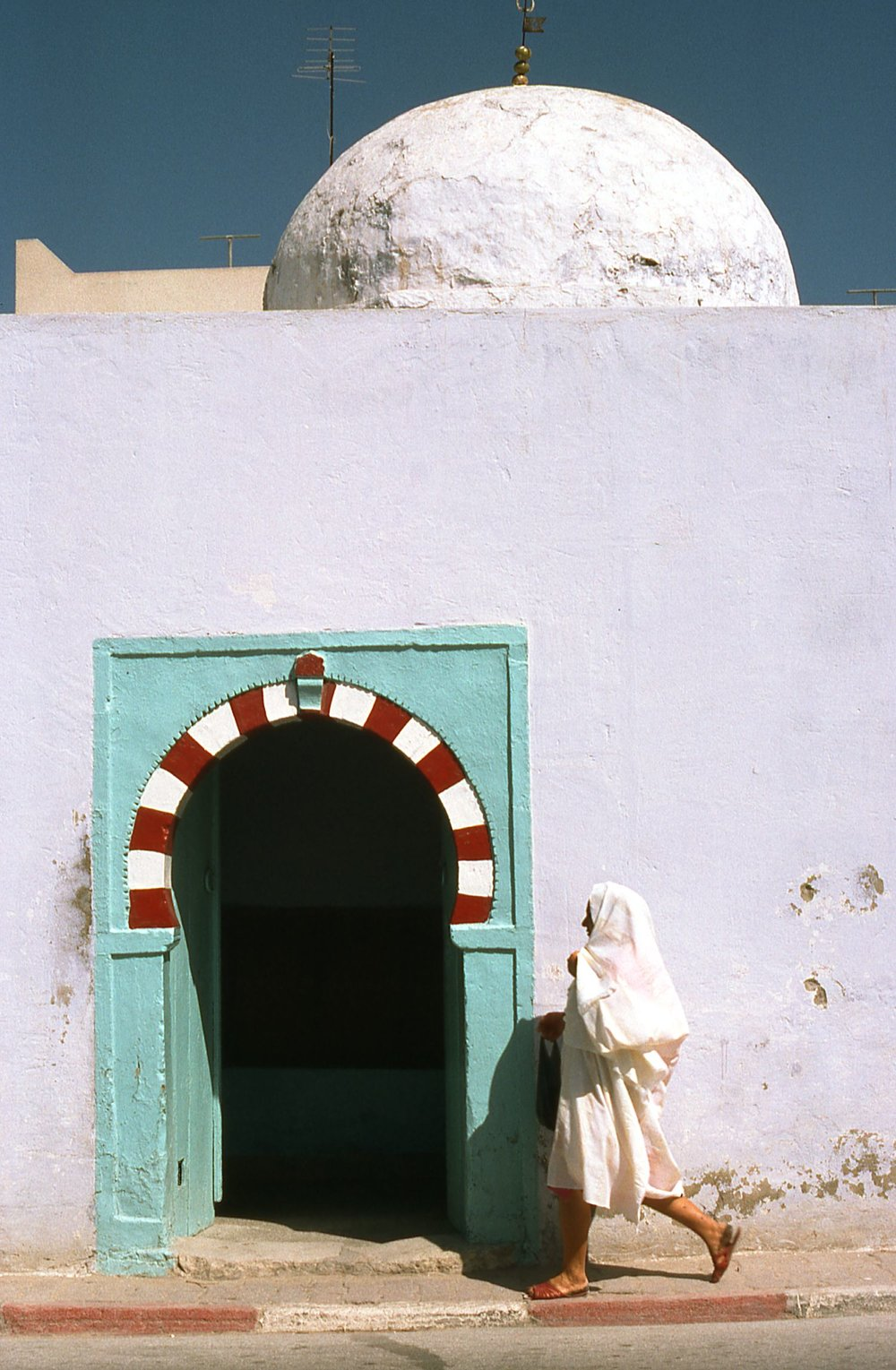 Tunisia | Arab woman an arabic door | photo sandrine cohen