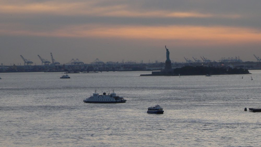 New York | Statue of Liberty and boats at evening | photo sandrine cohen