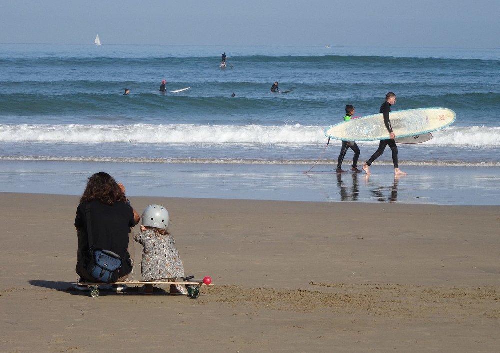 Hendaye Plage | Mère et enfant assisent sur skatebord regardent l'océan | Mother and daughter sit on a skateboard look at the ocean | photo sandrine cohen