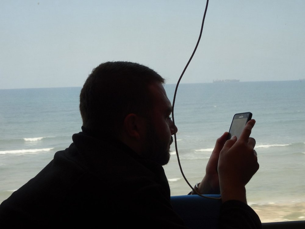 On the train from Haifa | Man with mobile at window | Seafront | photo sandrine cohen