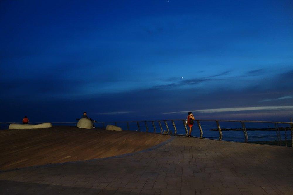 Tel-Aviv | Woman alone on the beach at night | Green light on the beach | photo sandrine cohen