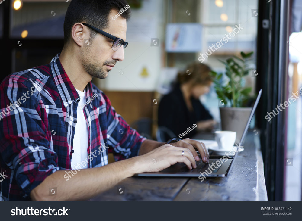 stock-photo-pensive-male-freelancer-in-eyewear-making-research-while-planning-online-project-sitting-in-666971140 (1).jpg