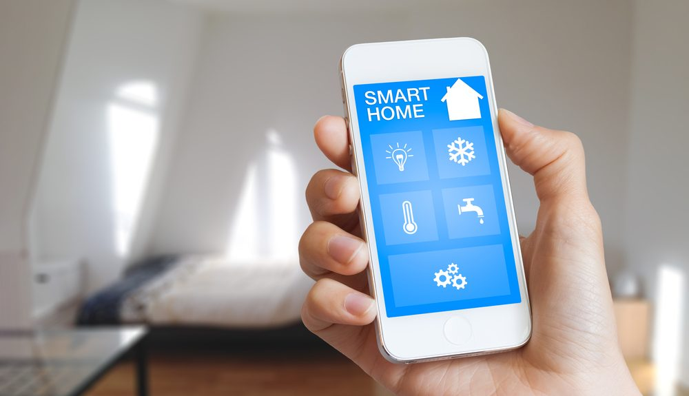 Smart-home-automation-app-on-smartphone-with-home-interior-in-background-e1463110857833.jpg
