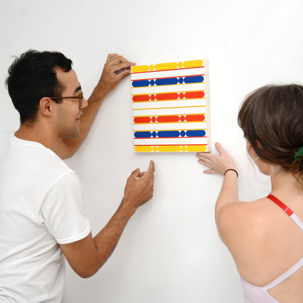 Kevin Umaña and Danni O'Brien hanging their end of residency show in August 2018.
