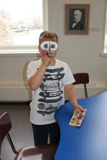 A grade 2 student on a tour for the Then and Now program in the hands-on part of the program.