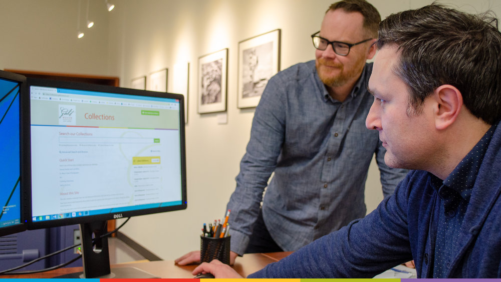 A photo of Archivist Andrew Chernevych and Collections Technician Kevin MacLean looking at the Galt's new online database website on a computer screen.