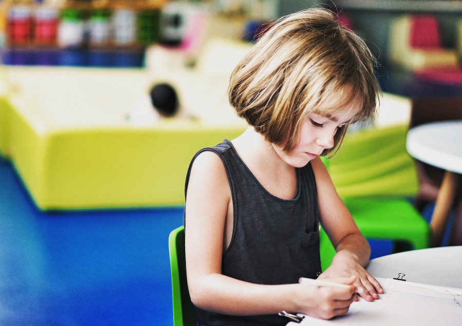 little girl coloring at a table