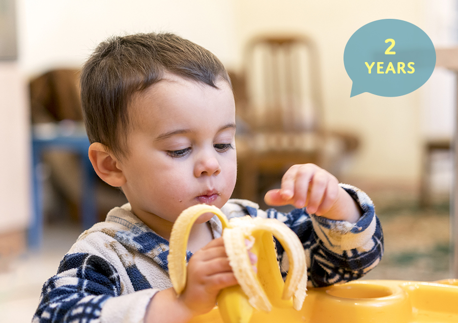 two year old boy peeling a banana