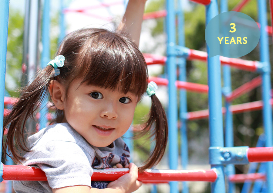 three year old girl playing on playground equipment