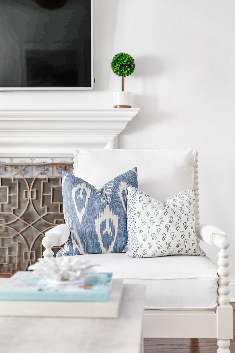 Product photography of white spindle chairs and accent pillows in a Riverside, Connecticut home.