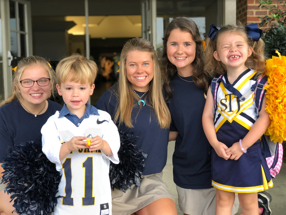 STJ cheerleaders greet some of our littlest Trojans on the first day of school.