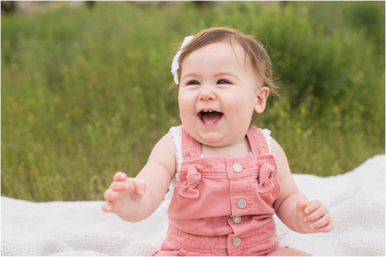 Baby girl laughing in a field of tall grass