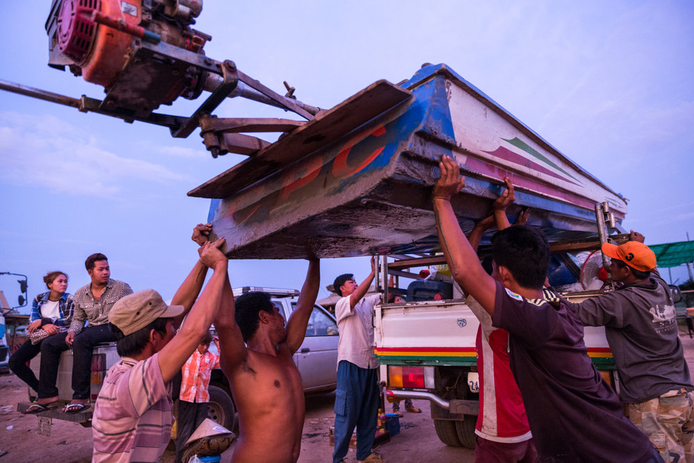 May 26, 2016 - Kampong Loung, Cambodia. People help Mai (45) and her family load their boat onto a waiting truck. The family is leaving Kampong Loung after having spent 20 years in the floating village, they will head to Vietnam where they are originally from. Low fish stocks due to climate change and over fishing on the lake has meant that the family can no longer make a living from fishing. © Nicolas Axelrod / Ruom