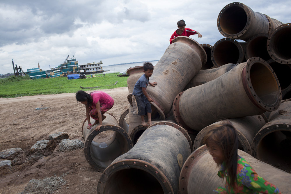 May 29, 2012 - Phnom Penh, Cambodia. Children play on pipes that were used to bring sand to Boeung Kak to fill in the lake. © Nicolas Axelrod / Ruom