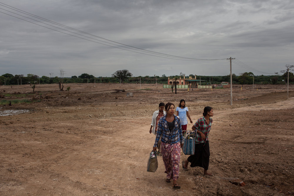 June 12, 2013 - Meikhtila, Myanmar. Women walk through Chan Aye's area, that was completely destroyed by the religious violence that took place in Meikhtila at the end of March 2013. © Nicolas Axelrod / Ruom