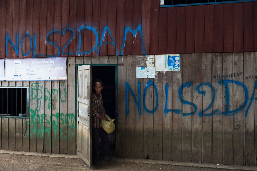 May 25, 2015 - Kbal Romeas, Cambodia. A man in front of his home that has been marked with 'No LS2 Dam'. When complete the nearby Lower Sesan 2 Dam will flood Kbal Romeas village. © Nicolas Axelrod / Ruom for Oxfam.