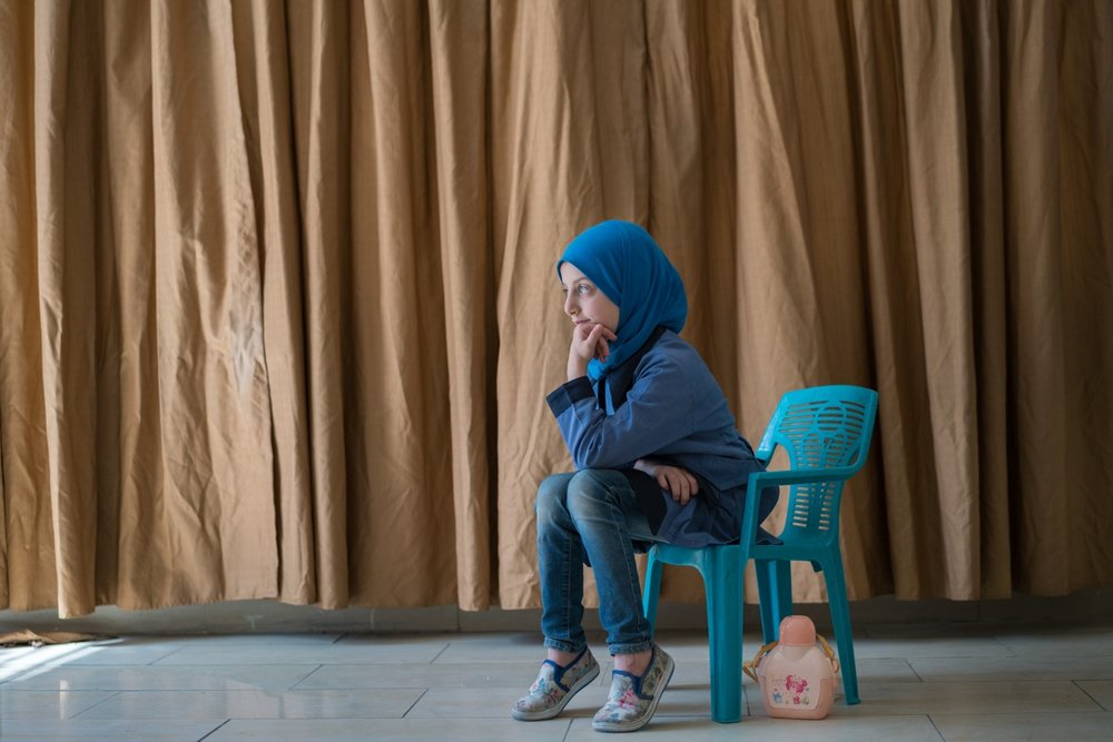"AMMAN, JORDAN - OCTOBER 1, 2015: Esma, 8, is a Syrian student at Khawla Bint Tha'laba Primary Girls School, a USAID-supported school located in an Amman suburb. She is one of around 65 Syrian students attending the USAID-supported school, which operates out of a rented building and struggles to accommodate the influx of refugees. In spite of the overcrowding, this school boasts a principal who is committed to accepting students, with one request for the parents: ""Please bring a chair with you."" Overall in Jordan, around 128,000 new Syrian students are crowding already overburdened classrooms. Teachers, struggling to achieve basic levels of proficiency in their classes, have the added burden of trying to accommodate and integrate new students who have suffered unthinkable trauma and may need special counseling and care. USAID supports schools like this across Jordan by providing teacher training and by developing an early grade reading and math diagnostic tool. The agency also builds and refurbishes schools throughout the country."