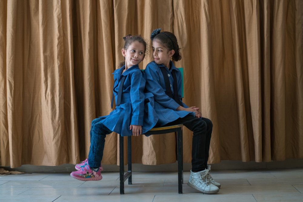 "AMMAN, JORDAN - OCTOBER 1, 2015: Maria (left) and her cousin Athari (right), are Syrian students at Khawla Bint Tha'laba Primary Girls School, a USAID-supported school located in an Amman suburb. They are one of around 65 Syrian students attending the USAID-supported school, which operates out of a rented building and struggles to accommodate the influx of refugees. In spite of the overcrowding, this school boasts a principal who is committed to accepting students, with one request for the parents: ""Please bring a chair with you."" Overall in Jordan, around 128,000 new Syrian students are crowding already overburdened classrooms. Teachers, struggling to achieve basic levels of proficiency in their classes, have the added burden of trying to accommodate and integrate new students who have suffered unthinkable trauma and may need special counseling and care. USAID supports schools like this across Jordan by providing teacher training and by developing an early grade reading and math diagnostic tool. The agency also builds and refurbishes schools throughout the country."