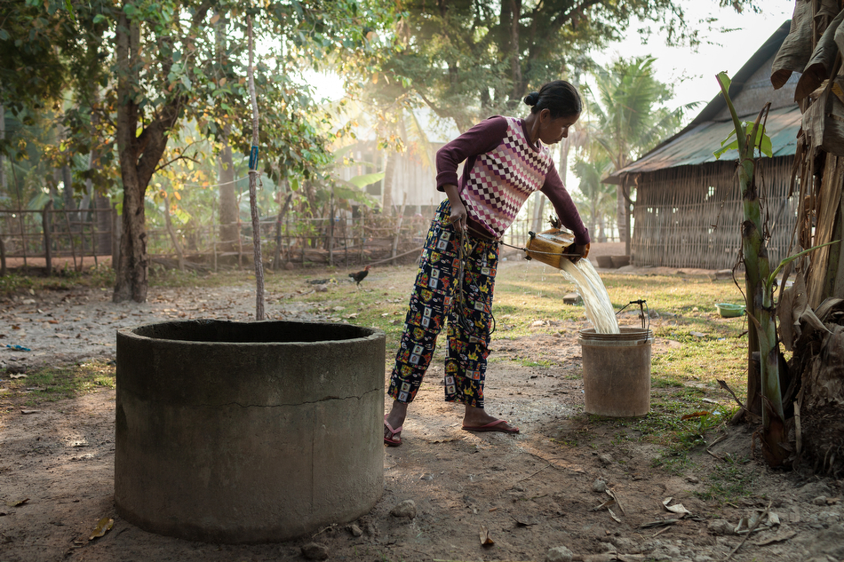 February 04, 2014 - Ta Reach Village (Kampot). Ms. Rin Ren (30) recollects water from her dug well. This is her main source for potable water, but it's only available during the wet season . © Thomas Cristofoletti / Ruom for SNV