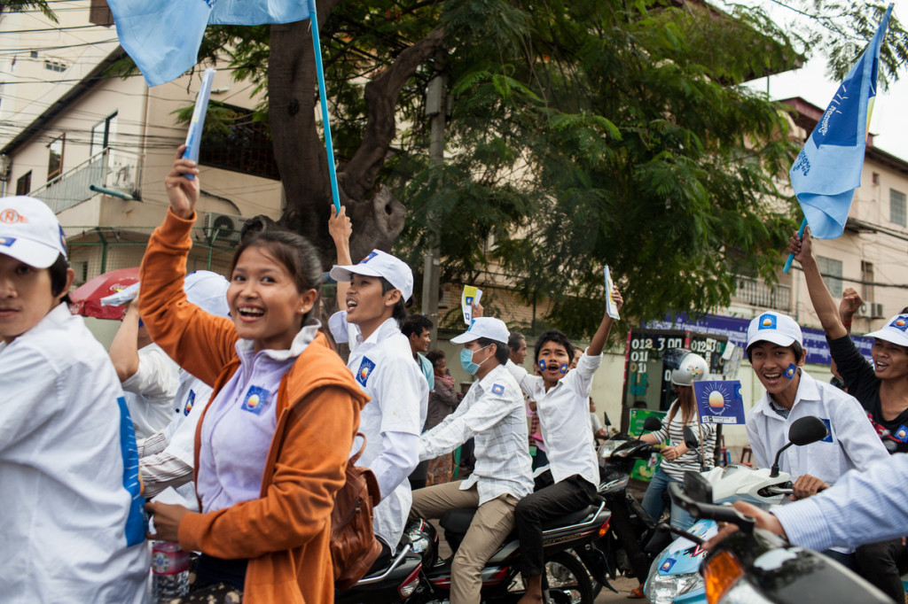 Youth, supporters the Cambodian National Rescue Party (CNRP) drive through the city campaigning on motorcycles. Phnom Penh, Cambodia. 29/06/2013 © Nicolas Axelrod/Ruom 2013