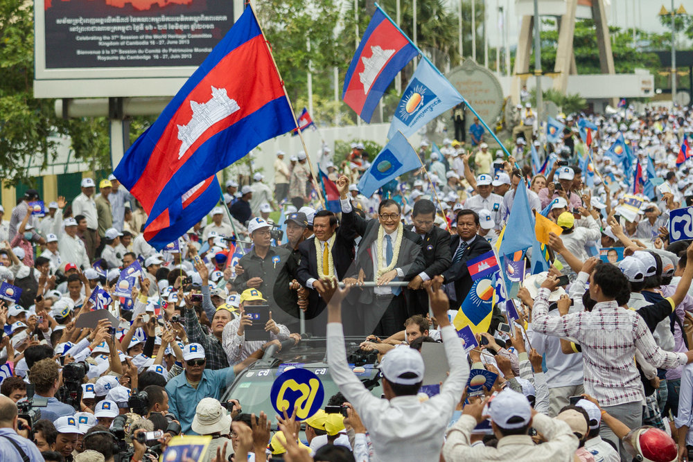 Sam Rainsy and Kem Sokha leave the airport of Phnom Penh surrounded by thousands of supporters of the CNRP party.